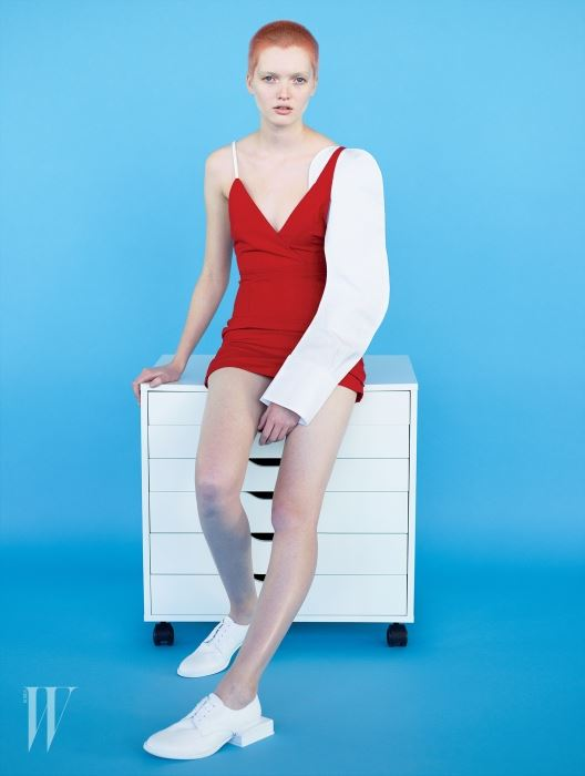 소매가 한쪽만 있는 비대칭 슬리브리스 드레스와 독특한 굽이 특징인 흰색 옥스퍼드 슈즈는 Jacquemus 제품.