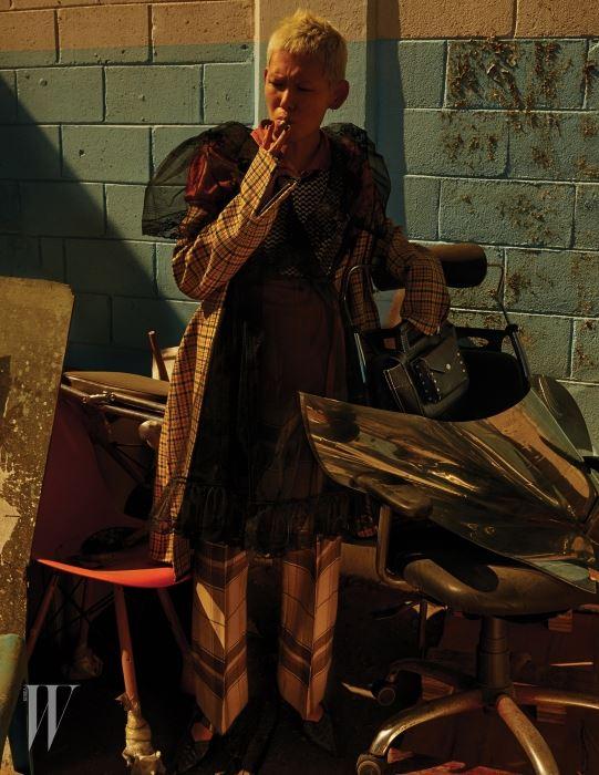 러플 장식 샤 드레스는 Miu Miu, 모래시계 실루엣의 체크 코트와 니트 크롭트 톱, 매니시한 체크 팬츠, 앞코가 뾰족한 버클 슈즈, 가죽 토트백은 모두 Celine, 황토색 셔츠는 Prada 제품.