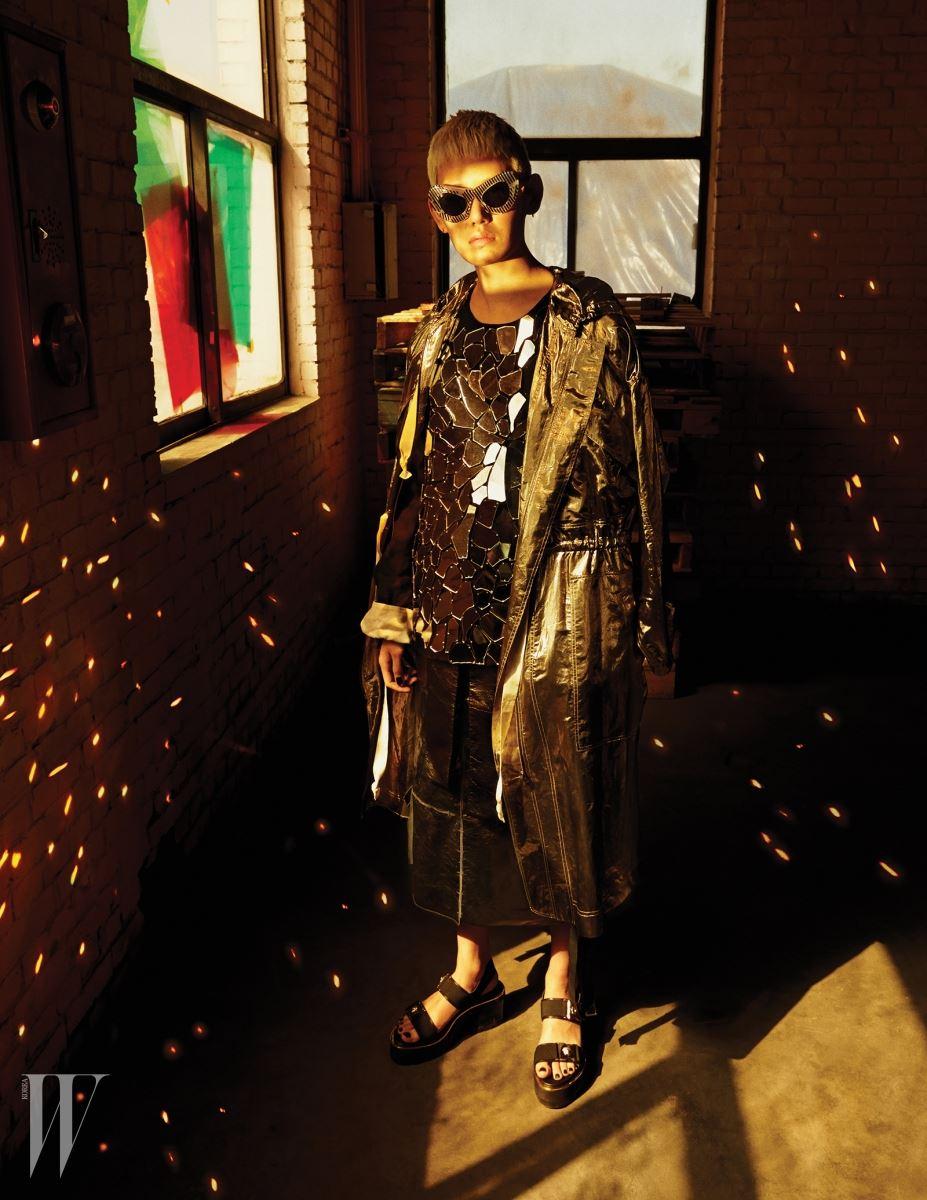 리본 장식의 가죽 미디스커트는 Salvatore Ferragamo, 거울 조각이 장식된 톱은 Loewe, 금빛 사파리 점퍼는 Isabel Marant, 버클 장식 플랫폼 슈즈는 Versace, 줄무늬 프레임의 캐츠아이 선글라스는 Louis Vuitton 제품.