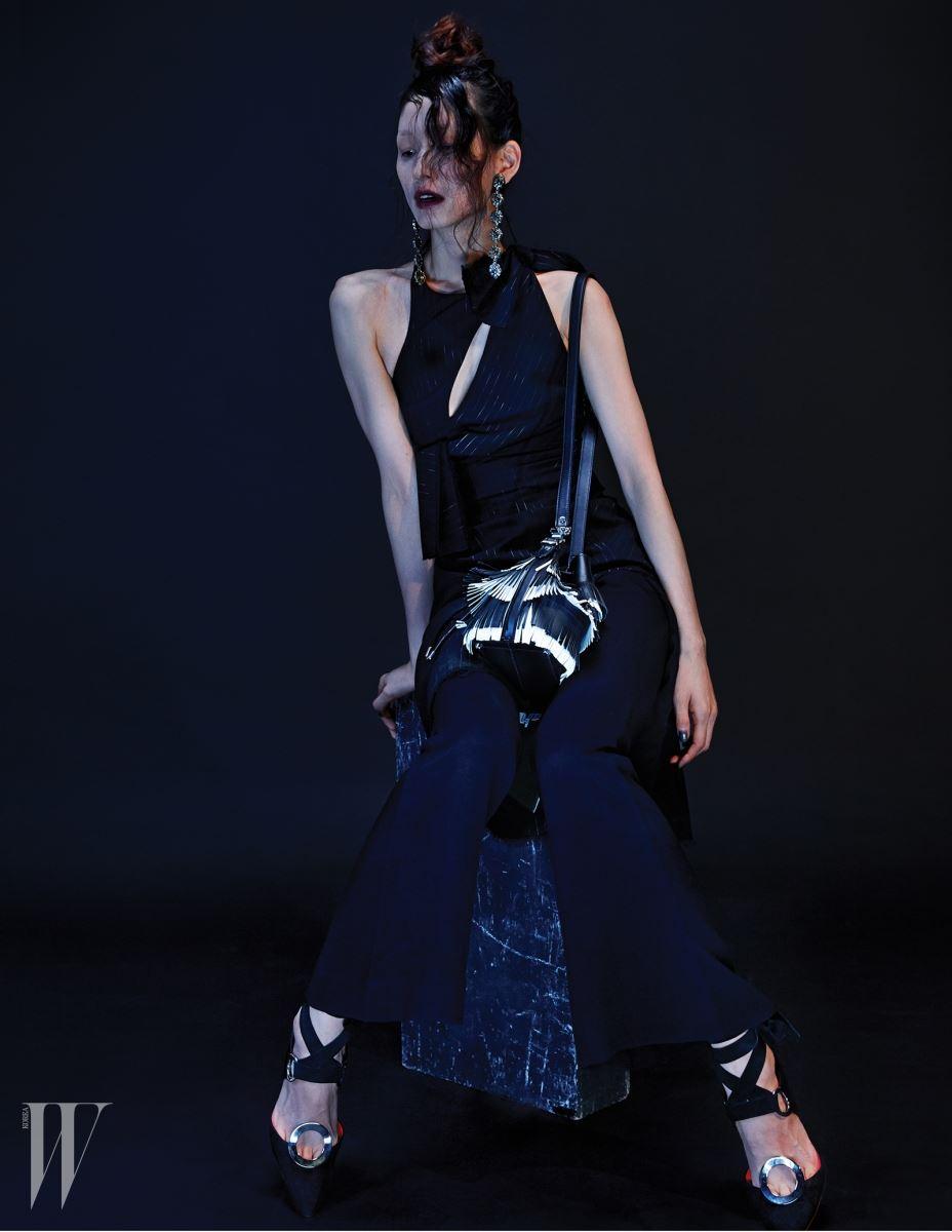깊은 슬릿 장식 드레스는 Versace, 밑단이 나팔 모양으로 퍼지는 팬츠, 원형 메탈 장식 슈즈와 프린지 장식 버킷백은 모두 Proenza Schouler, 앤티크한 드롭 이어링은 Gucci 제품.