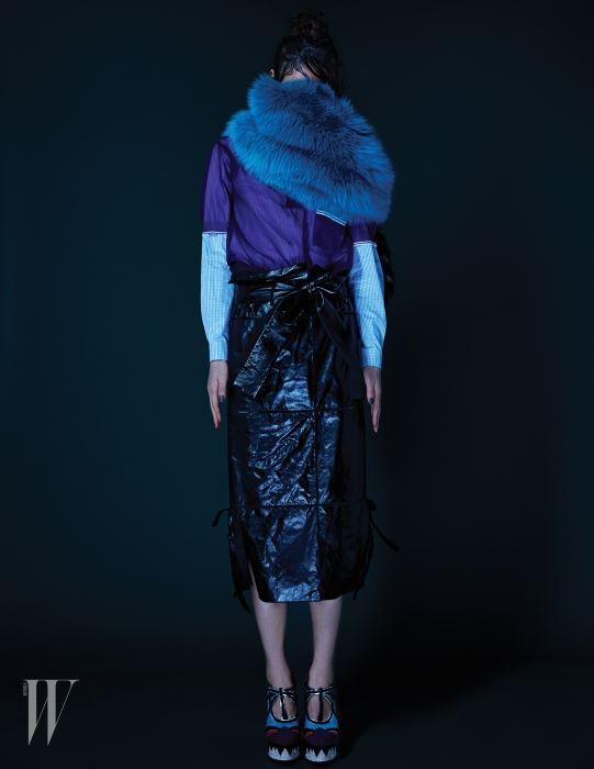 안에 입은 체크 셔츠와 보라색 폴로 셔츠, 풍성한 모피 스톨, 크리스털이 장식된 플랫폼 슈즈는 모두 Miu Miu, 리본 장식의 가죽 미디스커트는 Salvatore Ferragamo 제품.