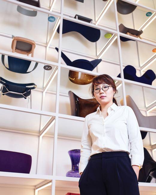 를 기획한 이여운 큐레이터가 다채로운 색상의 의자들 앞에 서 있다.