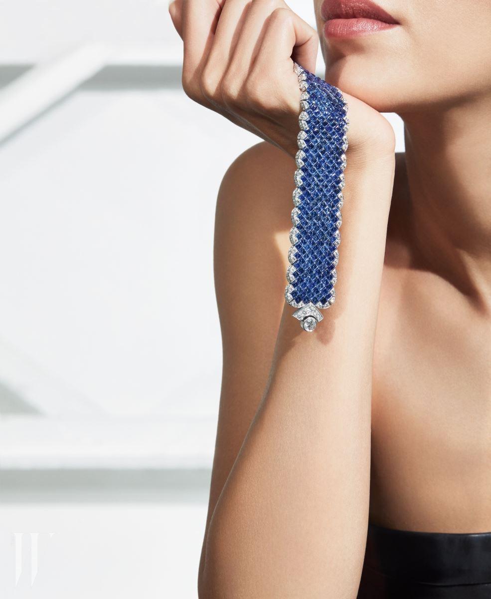 모델이 손에 든 265개에 달하는 스퀘어컷 사파이어 세팅이 매혹적인 시그너처 얼팀 팔찌.