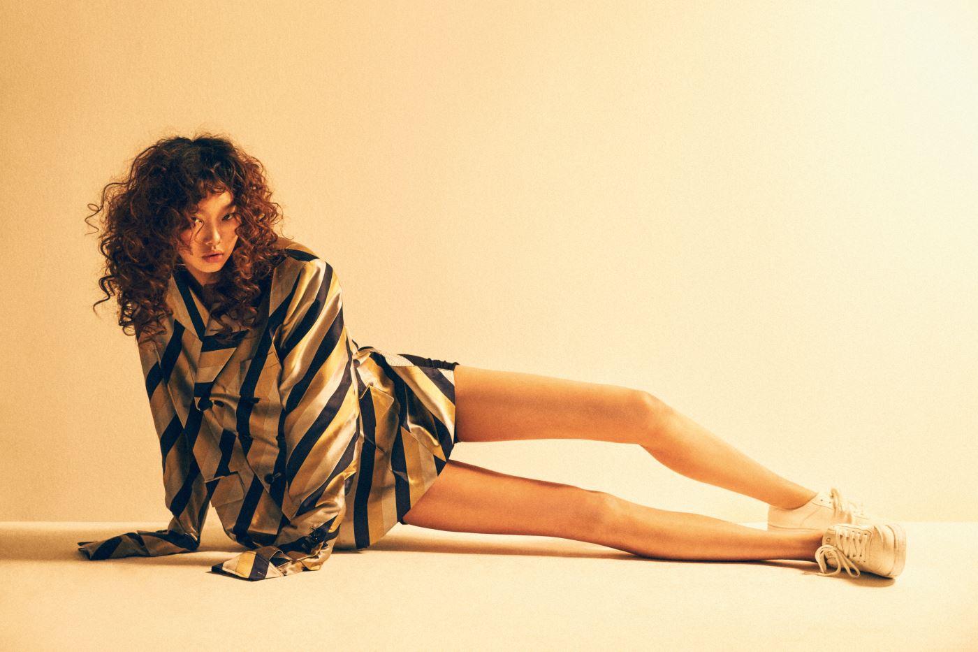 담대한 줄무늬 패턴의 박시한 재킷, 담백한 흰색 스니커즈는 Sewing Boundaries 제품.
