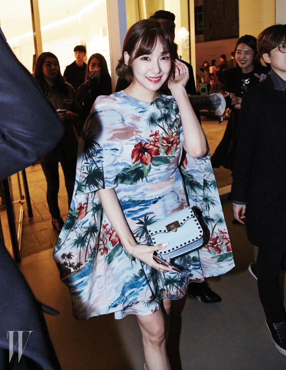 소녀시대의 티파니는 한 폭의 수채화를 연상시키는 풍부한 색감과 프린트가 멋진 케이프 형태의 원피스와 스터드 장식 핸드백을 선택했다. 제품은 모두 발렌티노.
