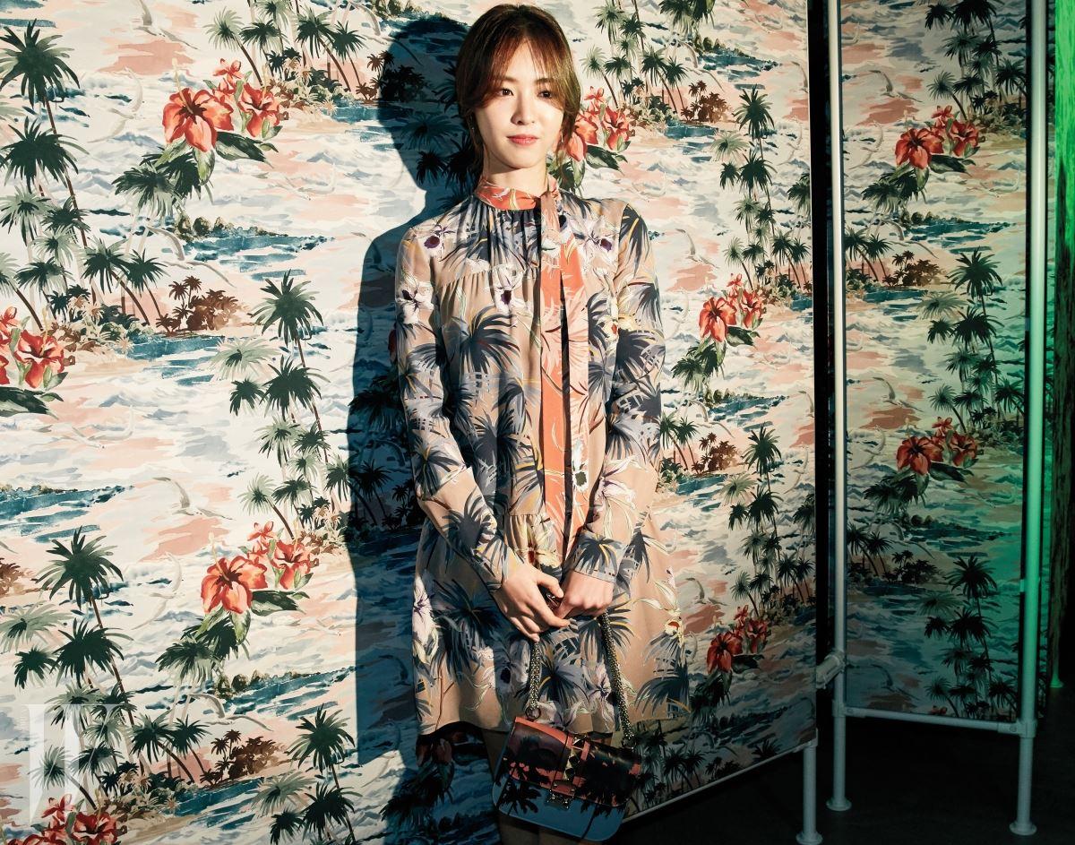 배우 이연희는 하와이언 쿠튀르 컬렉션에서 스카프 형태의 네크라인이 돋보이는 톤다운된 원피스와 핸드백을 매치했다.