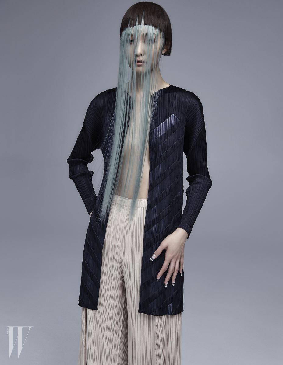 주름을 납작하게 누른 줄무늬 카디건, 살색 주름 바지는 Pleats Please 제품.