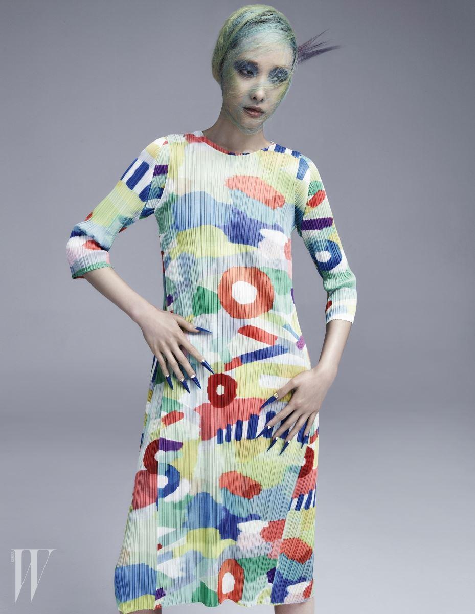 추상적인 도형이 그려진 튜닉과 겹쳐 입은 민소매 드레스는 Pleats Please 제품.
