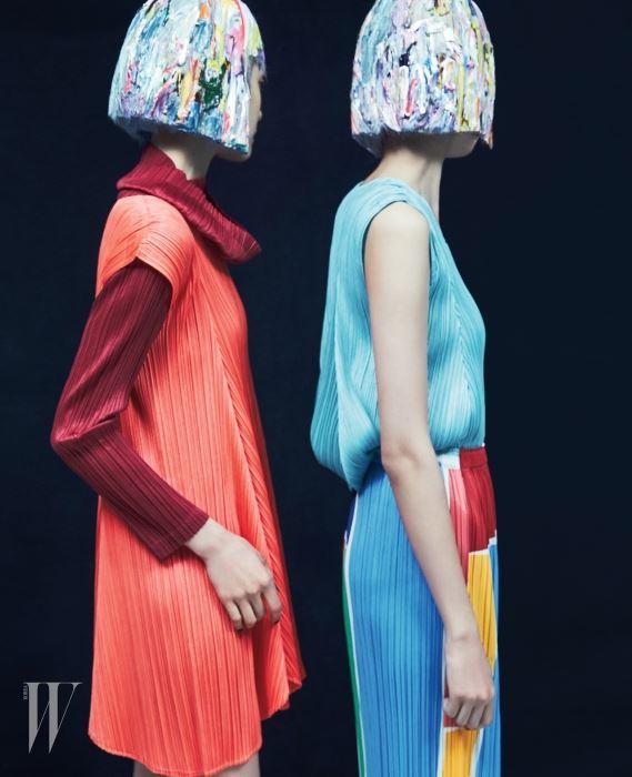 자주색 풀오버 튜닉과 겹쳐 입은 주황색 드레스, 하늘색 톱과 컬러 블록 프린트의 스커트는 모두 Pleats Please 제품.