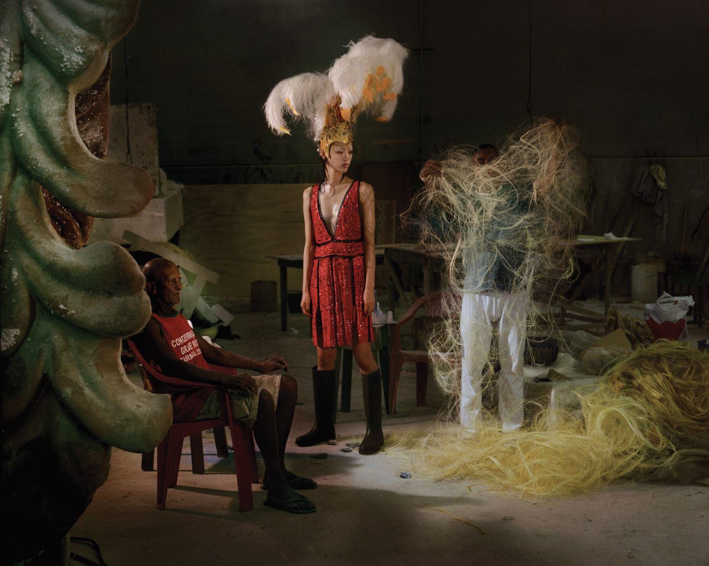 붉은색 시퀸 장식 드레스는 Emilio Pucci, 카키색 레인 부츠는 Saint Laurent 제품. 깃털 장식의 헤드피스는 삼바 학교(Samba School) 협찬 제품.