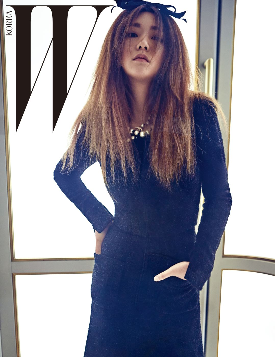 주머니가 장식된 검은색 미디 드레스, 그 위로 겹쳐 입은 펄감이 가미된 재킷, 큼지막한 진주 네크리스, 리본 헤어핀은 모두 Chanel 제품.