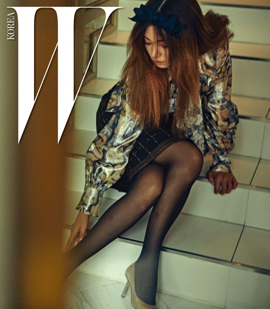 카멜리에와 고양이, V자 손 모양 등 귀여운 이모티콘이 담긴 메탈릭한 타이 장식 슬리브리스 셔츠, 셔츠와 겹쳐 입은 셔츠 블라우스, 측면을 지퍼로 조절할 수 있는 트위드 스커트, 투톤 슈즈, 리본 헤어핀은 모두 Chanel 제품.