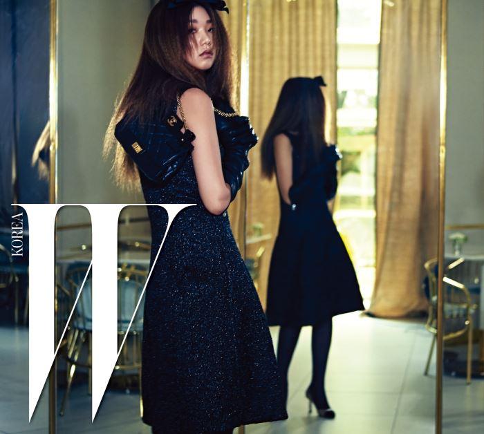 반짝이는 펄감이 가미된 슬리브리스 드레스, 지퍼 장식 장갑, 더블 C 로고가 장식된 체인 백, 투톤 슈즈, 리본 헤어핀은 모두 Chanel 제품.
