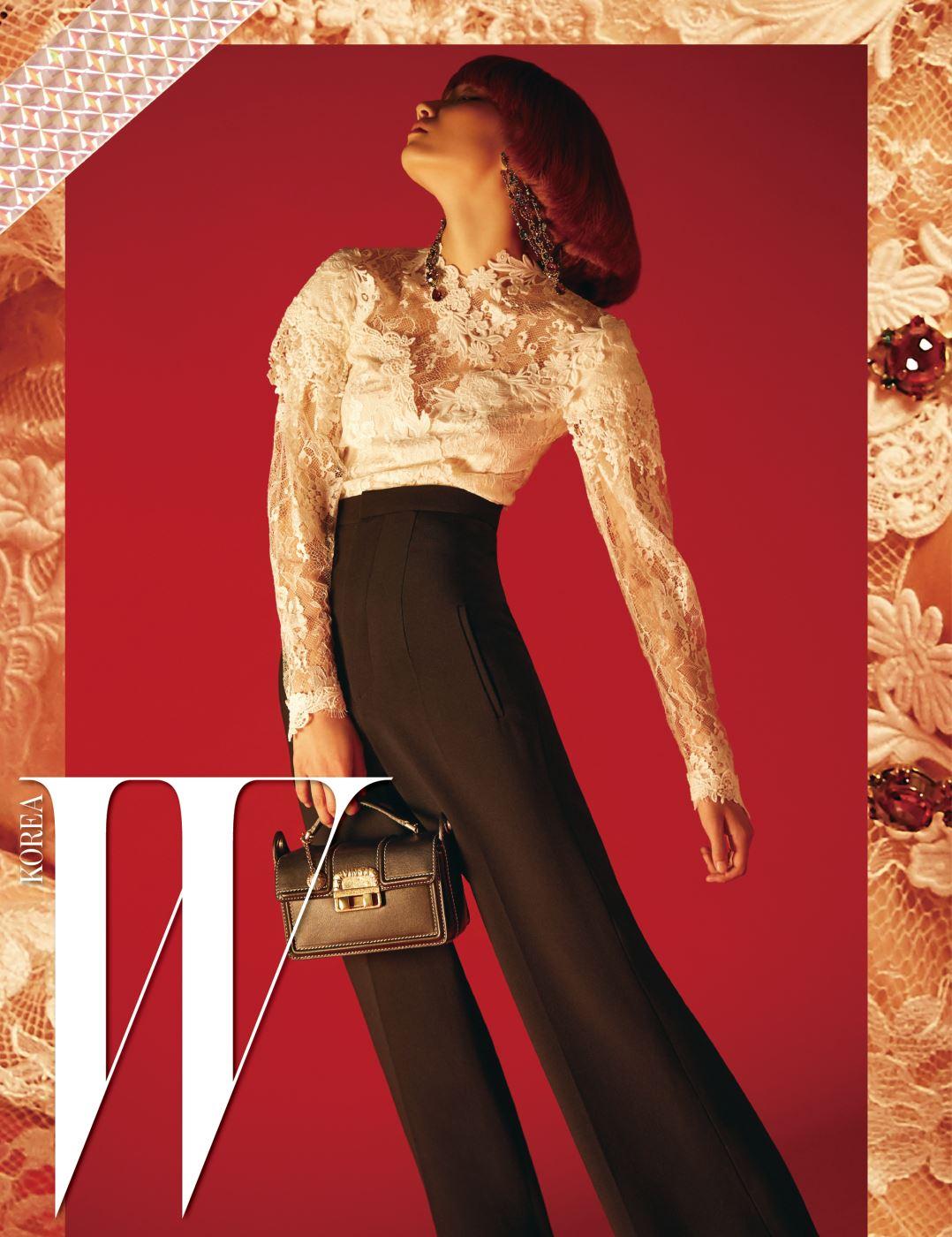 섬세한 크림색 레이스 소재의 블라우스, 드라마틱한 실루엣을 그리는 하이웨이스트 팬츠, 큼직한 크리스털 이어링, 스티치 장식과 앤티크한 락 장식이 돋보이는 지지(Jiji) 백은 모두 Lanvin 제품.