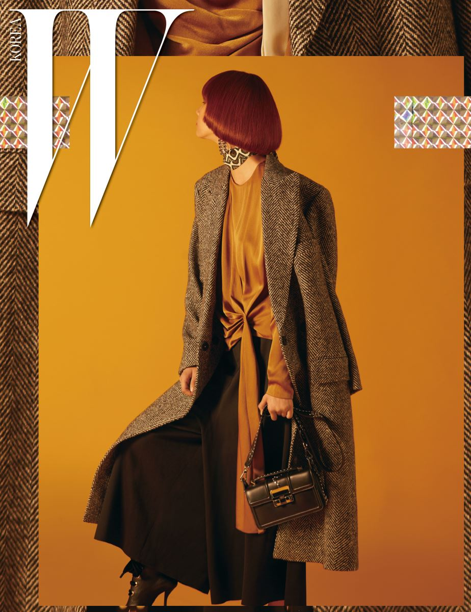 매니시한 디자인의 헤링본 코트, 매듭 장식이 아름다운 새틴 소재의 톱, 풍성한 검정 팬츠, 레이스업 슈즈, 지오메트릭 패턴의 프티 스카프, 크리스털 이어링, 스터드 장식이 돋보이는 지지(Jiji) 백은 모두 Lanvin 제품.