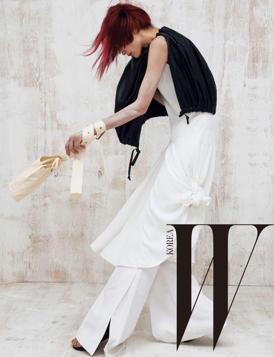 비대칭으로 묶어 연출한 드레스와 트임 장식 플레어 팬츠, 가죽 케이프와 위트 있는 주머니 가방, 샌들은 모두 Céline 제품.