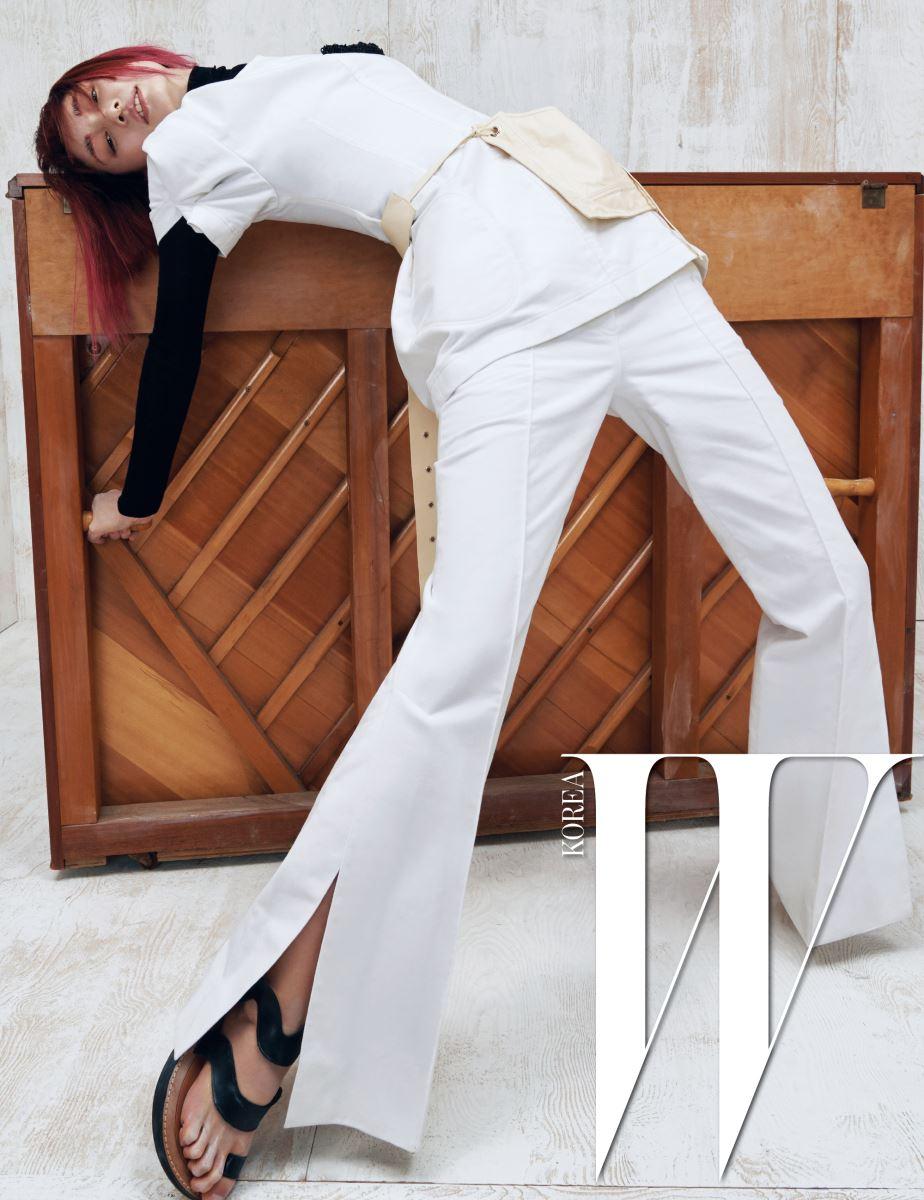 볼륨 있는 소매가 인상적인 톱과 터틀넥 톱, 트임 장식 팬츠, 벨트로 연출한 주머니 가방, 샌들은 모두 Céline 제품.