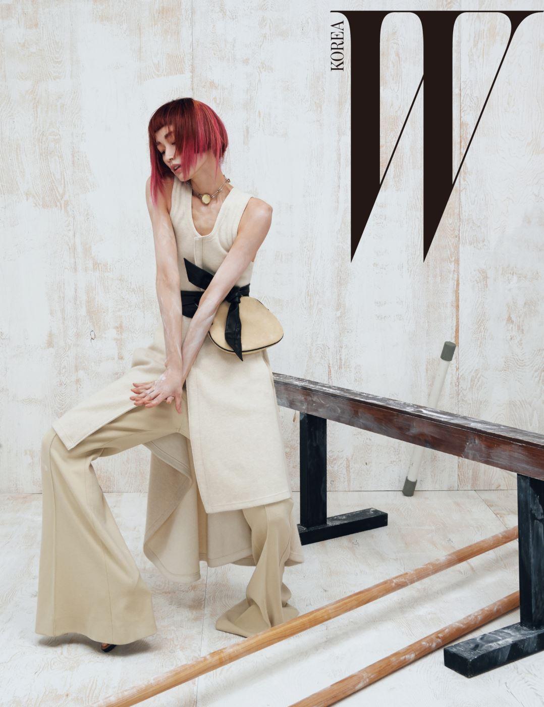 롱 A 라인 실루엣의 니트 톱과 플레어 팬츠, 허리에 묶어 연출한 스웨이드 소재 백, 목걸이는 모두 Céline 제품.