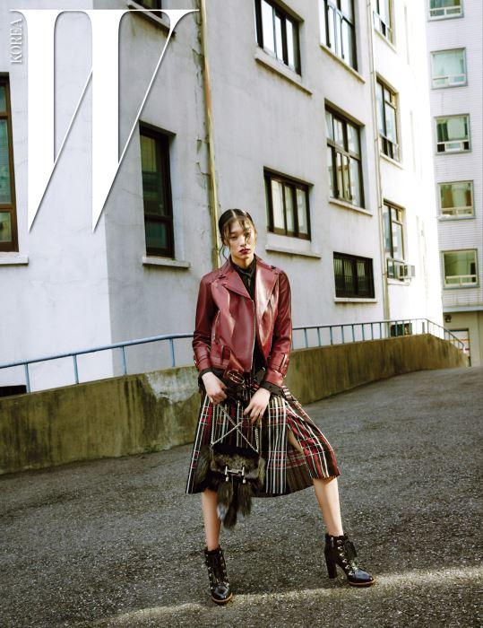 강한 색감이 돋보이는 풍성한 니트, 스티치 장식이 들어간 검은색 가죽 스커트, 태슬이 달린 스티치 백, 태슬 장식의 체인 목걸이는 모두 Tod's 제품.