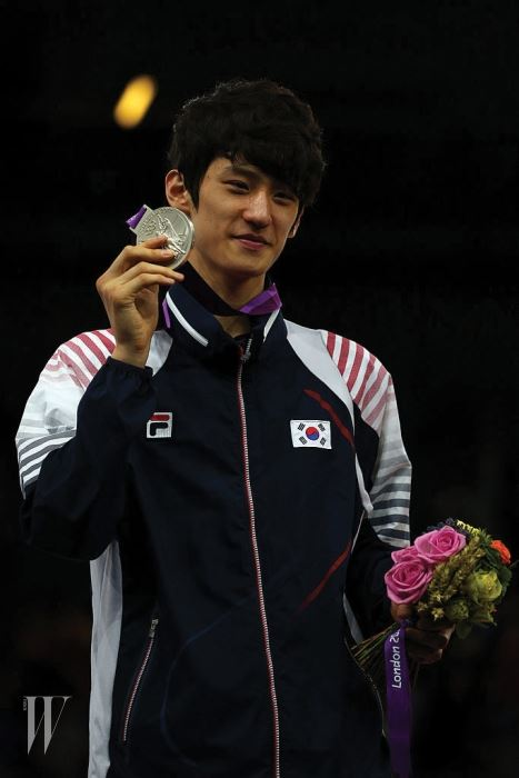 LONDON, ENGLAND - AUGUST 08:  Silver medallist Daehoon Lee of Korea celebrates during the medal ceremony for the Men's -58kg Taekwondo on Day 12 of the London 2012 Olympic Games at ExCeL on August 8, 2012 in London, England.  (Photo by Hannah Johnston/Getty Images)