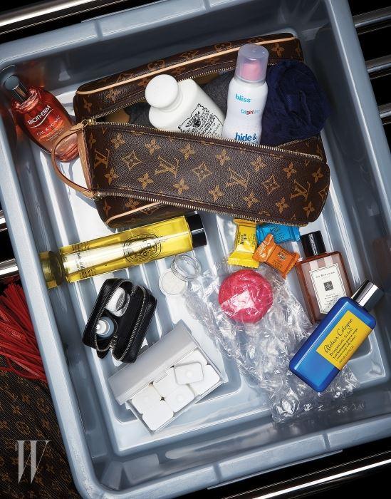 모노그램 패턴의 토일렛 파우치와 트레이 옆 플리츠 소재 트라이앵글 워리어 백은 루이 비통, 렌즈 케이스는 프라다 제품.