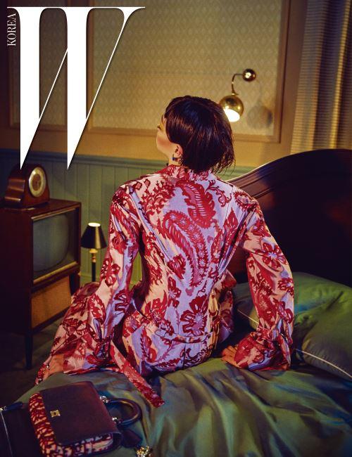 허리선이 돋보이는 번아웃 자카드 문양의 코트 드레스, 시그너처 파우치가 부착된 핸드백, 이어링과 드롭 이어커프, 레이어드한 링은 모두 Dior 제품. 침대 프레임은 SIMMONS Collectionon 벨로Ⅱ, 그린 컬러의 베딩은 KENOSHA HOME by SIMMONS 제품.