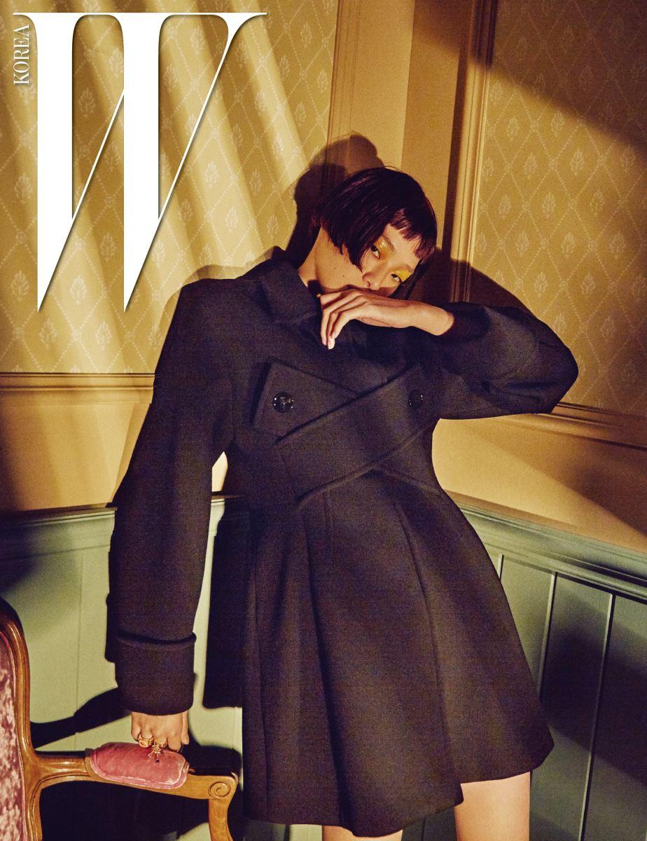 버튼 디테일의 블랙 코트, 레이어드한 링은 Dior 제품.