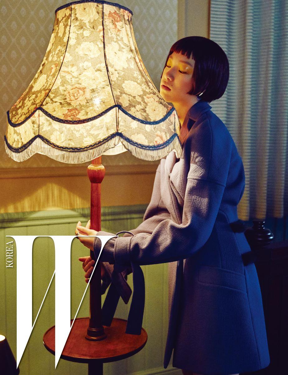 소매 부분의 스트랩, 뒤에 퍼 트리밍이 포인트인 코트, 이어링과 드롭 이어커프, 레이어드한 링은 모두 Dior 제품.