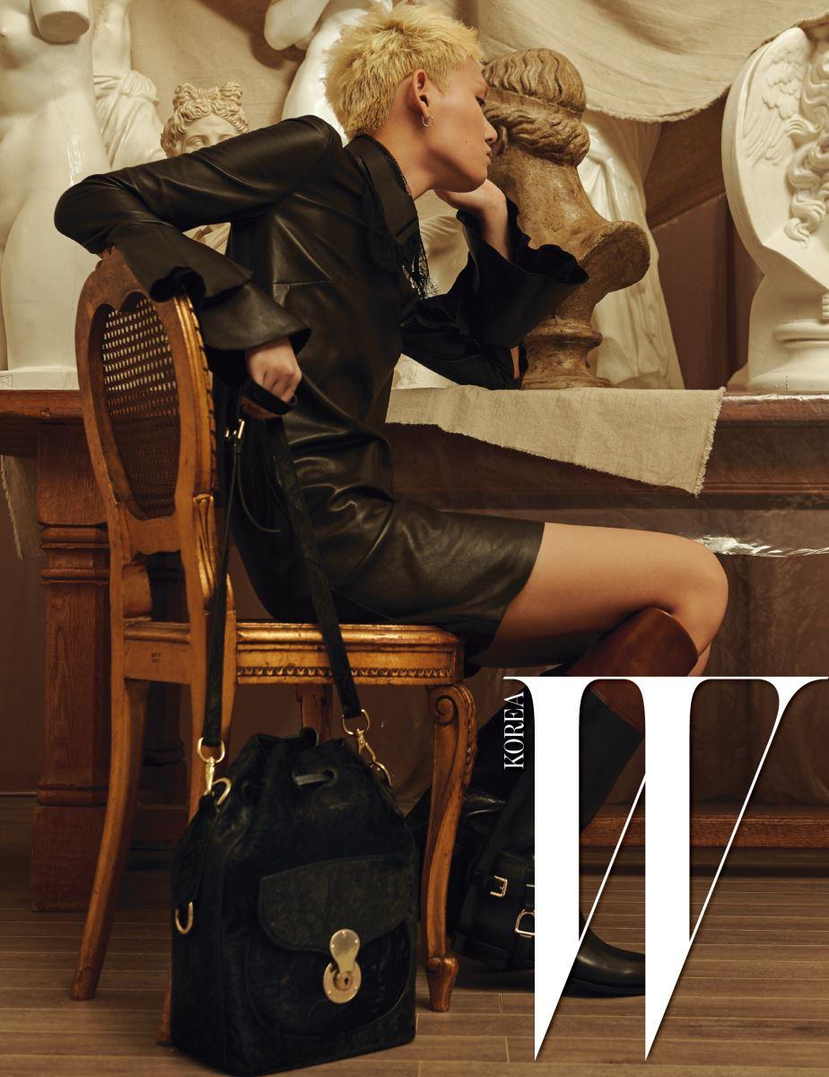 레이스로 장식된 가죽 칼라 목걸이와 커다란 러플 소매가 특징인 검정 가죽 드레스, 골드 잠금장치의 송치 드로스트링 백, 롱 부츠는 모두 Ralph Lauren Collection 제품.