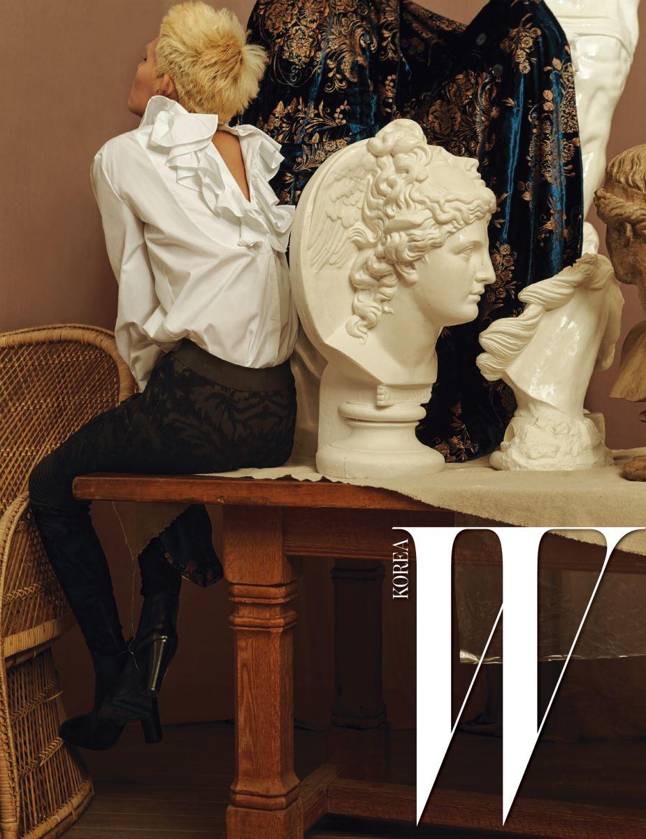 등과 소매의 러플로 여성스러움을 더한 셔츠와 오리엔탈 패턴의 검정 벨벳 니트 팬츠, 검은색 앵클부츠, 석고에 걸쳐놓은 자수 벨벳 롱 코트는 모두 Ralph Lauren Collection 제품.