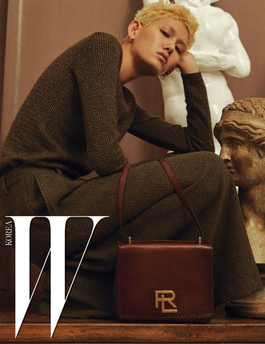 갈색 헤링본 니트, 체크 패턴의 통 넓은 팬츠와 로고 장식이 돋보이는 짙은 갈색 숄더백은 모두 Ralph Lauren Collection 제품.