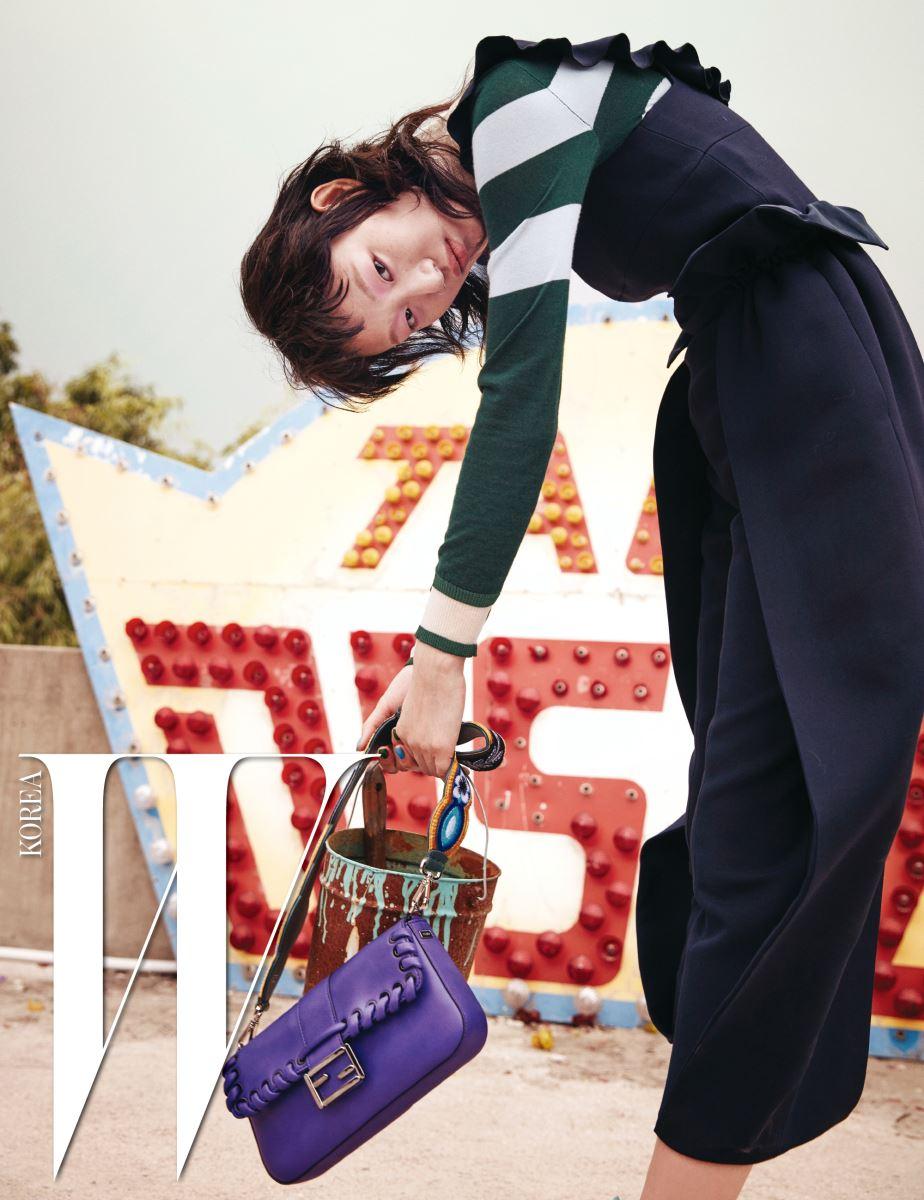 경쾌한 줄무늬 니트 톱, 러플 장식이 돋보이는 실크 울 소재 점프슈트, 꽃 패턴의 보태니컬 가든 스트랩 유(Strap You) 어깨끈을 더한 보라색 바게트(Baguette) 백은 모두 Fendi 제품.
