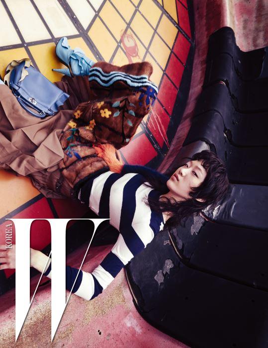 줄무늬 캐시미어 톱, 옆면에 코튼 울 소재의 주름 장식을 더한 채 정교하게 염색한 밍크털 퀼트 스커트, 어깨에 두른 퍼 스톨, 러플 장식이 여성스러움을 더하는 푸른색의 미니 피카부(Mini Peekaboo) 백, 하늘색 가죽 타이츠와 뮬은 모두 Fendi 제품.