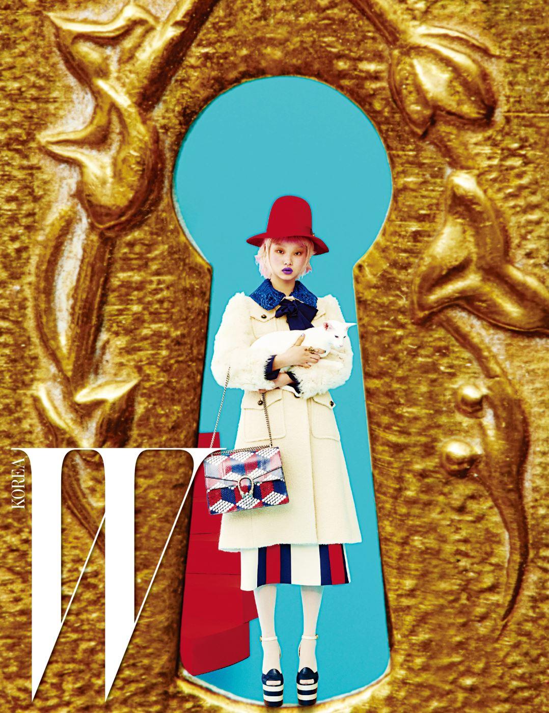 위트 있는 형태의 붉은색 펠트 모자, 보 장식의 푸른색 칼라를 더한 순백의 코트, 줄무늬 스커트, 크림색 타이츠, 플랫폼 샌들, 진주 장식 반지, 그리고 큐브 프린트의 디오니서스(Dionysus) 백은 모두 Gucci 제품.