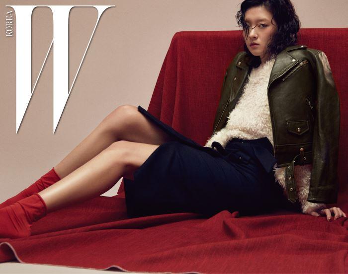 짙은 카키색의 심플한 바이커 재킷, 부드러운 질감의 크림색 풀오버, 버튼 장식의 무릎길이 스커트는 모두 Iro 제품.