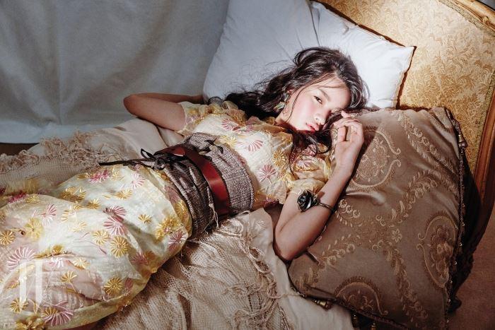 꽃자수가 장식된 오간자 드레스, 트위드 코르셋 벨트와 가죽 벨트, 메탈 장미 뱅글은 모두 Prada, 원석을 장식한 장미 귀고리는 Bimba Y Lola 제품.