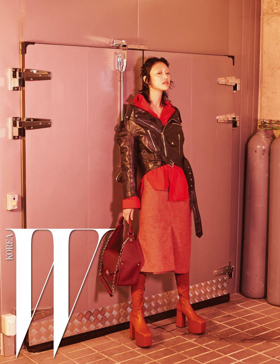 검은색 스윙 바이커 재킷, 안에 입은 매니시한 빨강 셔츠, 하운즈투스 체크 킥 스커트, 캐멀색 플랫폼 사이하이 부츠, 갈색 툴 숄더 플랩 백은 모두 Balenciaga 제품.
