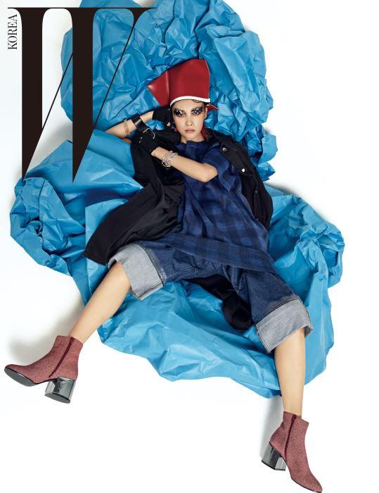 헤드피스로 연출한 클러치, 검정 데님 코트, 파랑 체크무늬 드레스, 크롭트 데님 팬츠, 부츠, 장갑, 오른팔의 버클 장식 클러치, 여러개 겹쳐 연출한 체인 팔찌는 모두 MM6 제품.