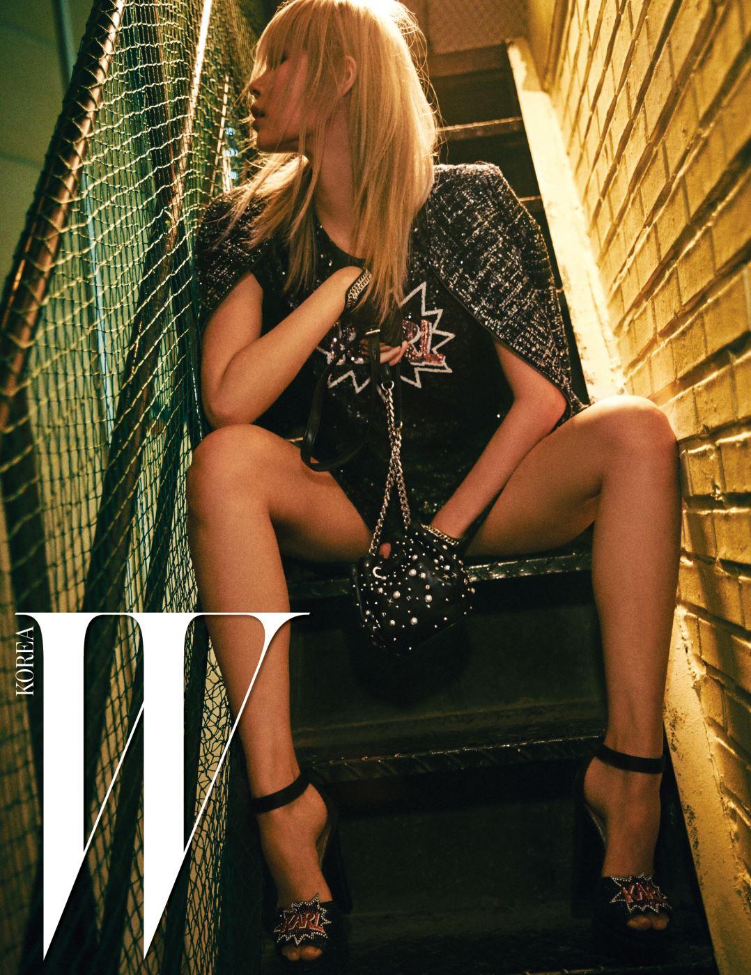 KARL 로고가 그려진 시퀸 장식의 미니 드레스, 어깨에 걸친 트위드 재킷, 반짝이는 플랫폼 샌들, 스터드 장식의 미니 버킷백, 체인 장식 장갑은 모두 Karl Lagerfeld 제품.
