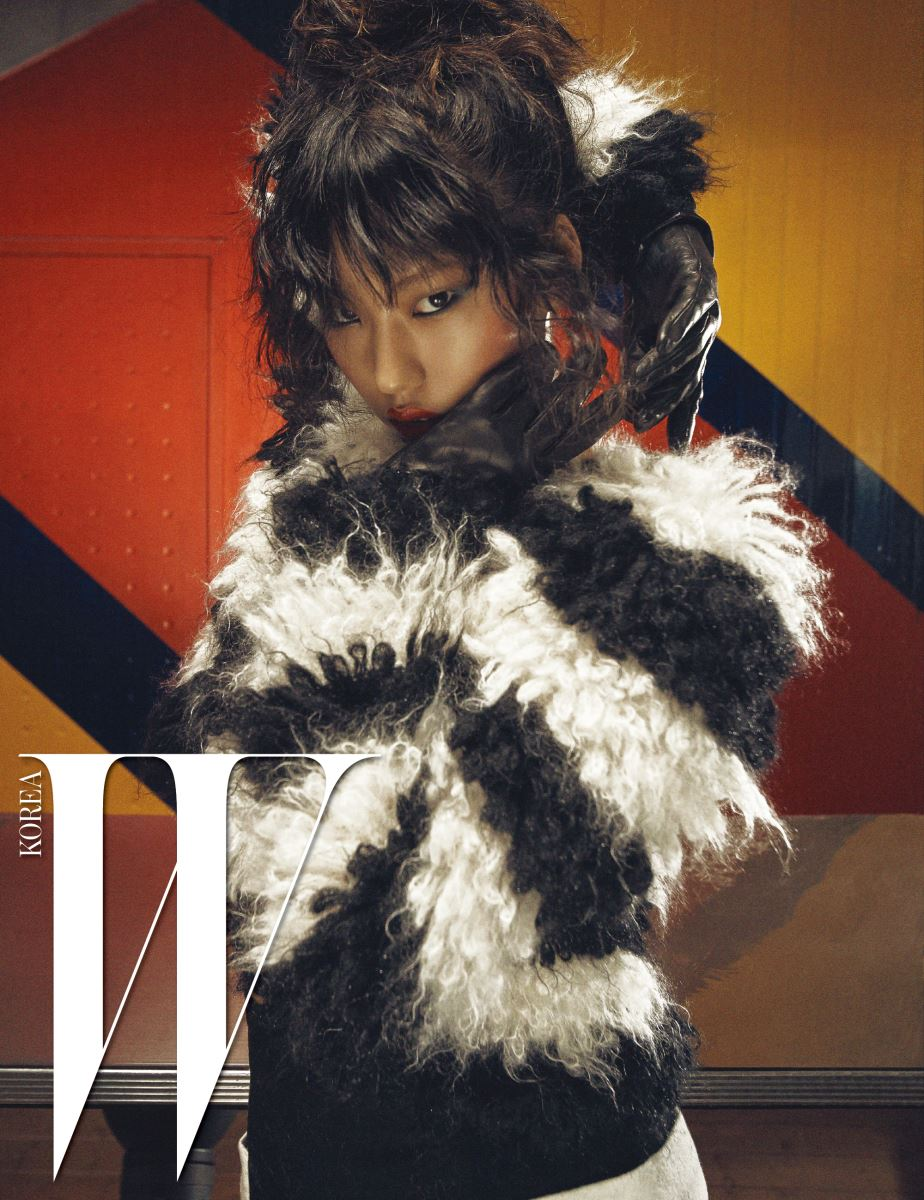 검은색과 흰색 줄무늬로 이루어진 풍성한 스웨터, 울 소재 미디스커트, 가죽 장갑 모두 Max Mara 제품.