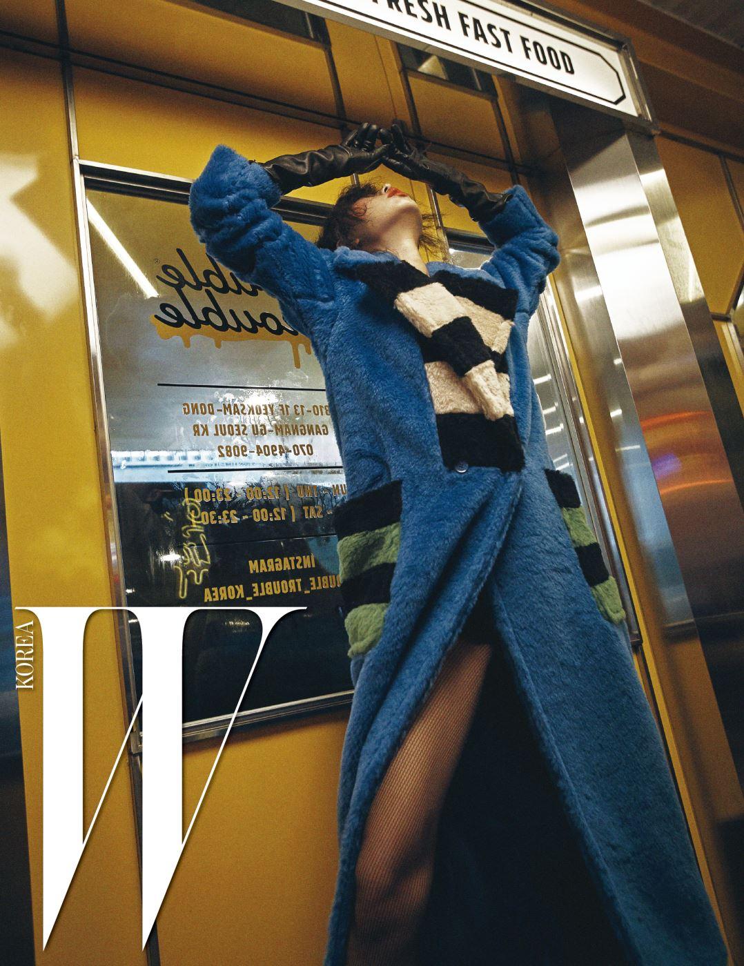 강렬한 색상 대비가 인상적인 푸른색 롱 코트는 Max Mara 제품.