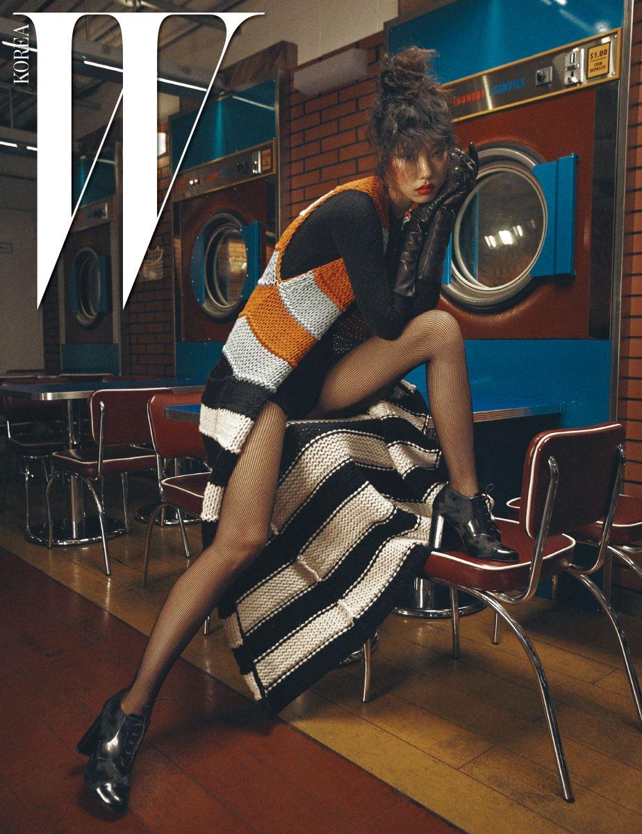 검은색 보디슈트와 색상 조합이 경쾌한 줄무늬 니트 베스트, 가죽 장갑과 레이스업 부티는 모두 Max Mara 제품.