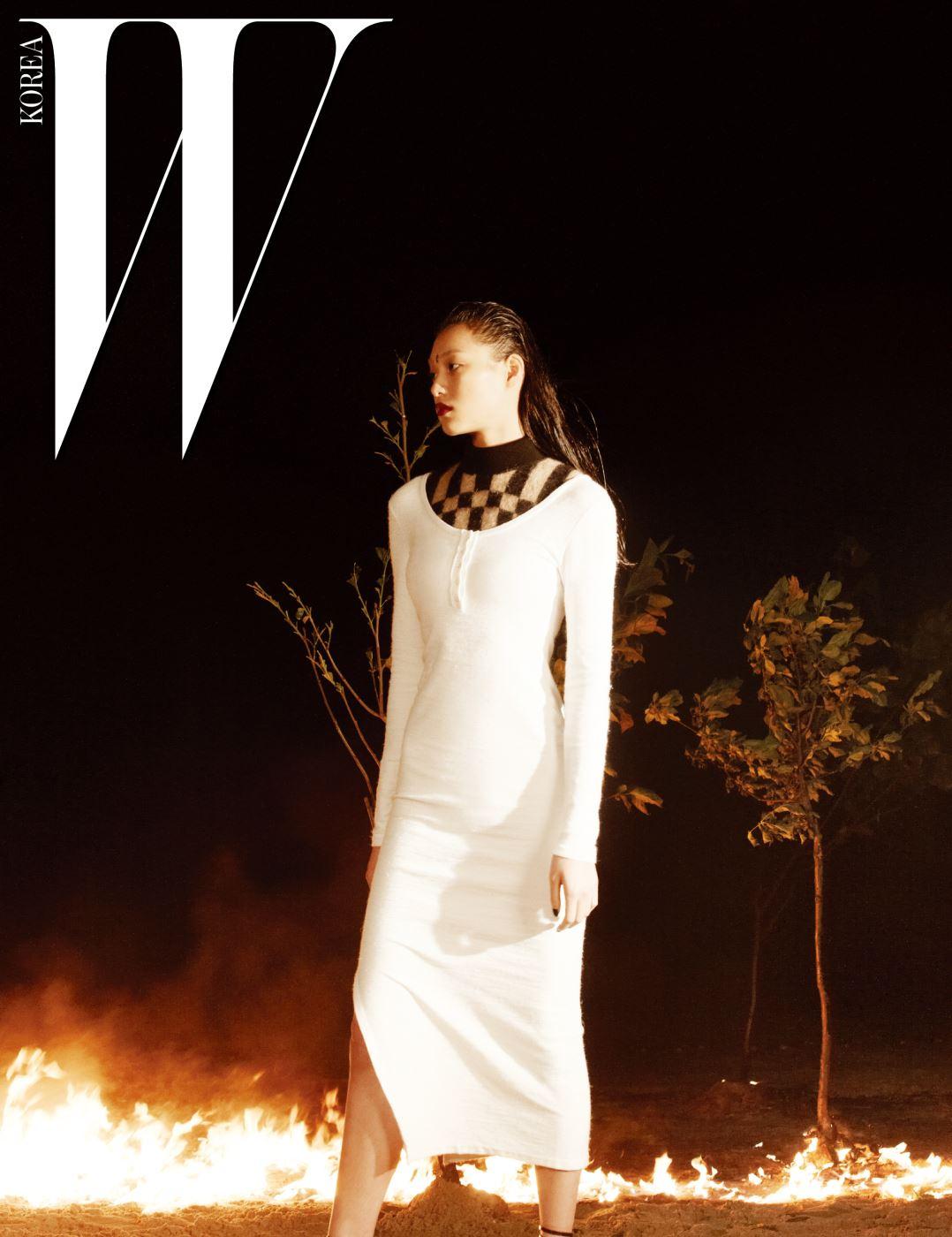 체크 무늬의 시스루 터틀넥 톱이 달린 하얀색 슬릿 드레스는 Loewe 제품.