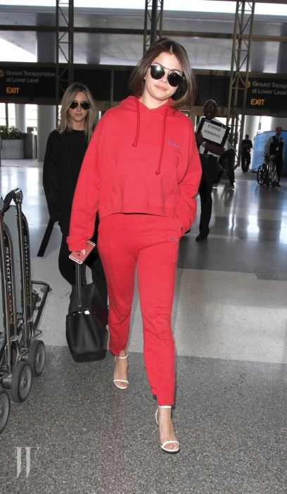 Selena Gomez is spotted in an all red Vetements hoodie and heels as she catches a flight out of Los Angeles while clutching on to her trusty iPhone.  Selena Gomez was seen flying out of LAX. Pictured: Selena Gomez Ref: SPL1241255  070316   Picture by: Sharky / Splash News Splash News and Pictures Los Angeles:310-821-2666 New York:	212-619-2666 London:	870-934-2666 photodesk@splashnews.com