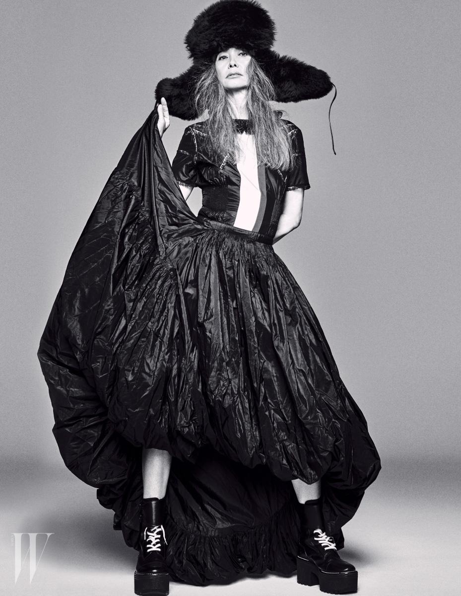 커다란 퍼 소재 코사크 햇, 비대칭적인 밑단 길이가 드라마틱한 드레스, 레이스업 워커는 모두 Louis Vuitton 제품.