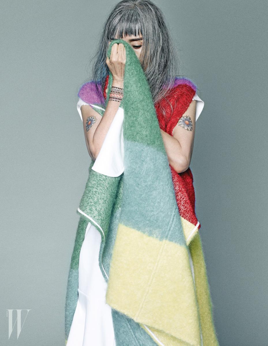 컬러풀한 모직 베스트는 Ports 1961, 러플 장식의 헴라인이 특징인 흰색 미니드레스는 Adidas Originals 제품.