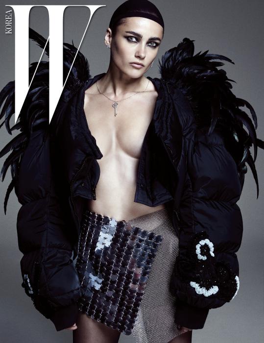 플래티넘, 18K 골드에 쿠션 컷 옐로 다이아몬드와 라운드 브릴리언트 화이트 다이아몬드가 세팅된 라운드 칼레이도스코프 키 펜던트 네크리스, 왼쪽 귀에 착용한 빅토리아 믹스드 드롭 이어링, 오른쪽 귀에 착용한 빅토리아 믹스트 클러스터 이어링은 모두 Tiffany&Co., 재킷은 Marc Jacobs, 스커트로 연출한 드레스는 Fanni Schiavani(Albright Fashion Library), 타이츠는 Alexander Wang 제품.