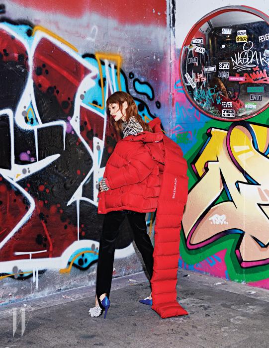 붉은색 후디 패딩 점퍼와 패딩 머플러, 화려한 메탈 장식 톱, 고리 장식 팬츠, 쿠튀르적 기교를 더한 새틴 펌프스는 모두 Balenciaga 제품.