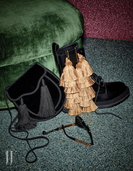 검정 벨벳 소재의 태슬 장식 숄더백은 Saint Laurent, 황금빛 태슬 장식이 강렬하게 시선을 끄는 레이스업 부츠는 Burberry, 금빛 메탈 장식이 카리스마를 더하는 선글라스는 Chanel 제품.