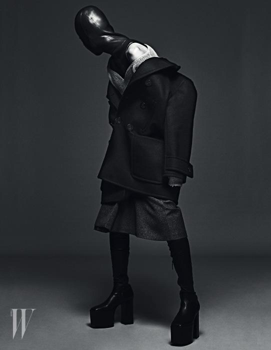 베이지색 하트넥 니트 톱, 남색 스윙 피코트, 회색 킥 스커트, 검정 플랫폼 사이하이 부츠는 모두 Balenciaga 제품.
